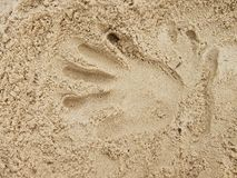 Male hand print in the salt sand on the beach. Royalty Free Stock Photo