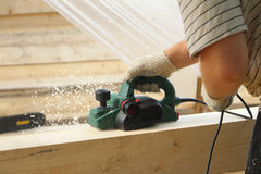 The male hand processes a bar an electric planer. Outdoors Stock Image