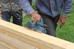 The male hand processes a wooden board an electric planer. Outdoors Royalty Free Stock Photo