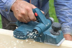 The male hand processes a wooden board an electric planer. Outdoors Stock Photo