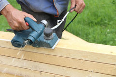 The male hand processes a wooden board an electric planer Stock Photography