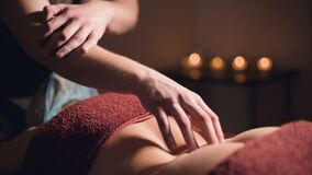 Male hand of a professional physiotherapist masseur doing lumbar massage to a female patient in a massage luxury room