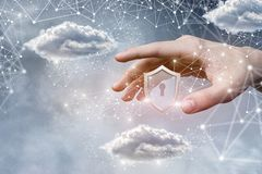 A male hand with protection shield and data clouds stock photo