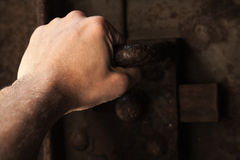 Male hand pull the handle of old rusted metal door Royalty Free Stock Photo