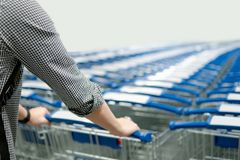 Male hand pulling shopping cart in supermarket. Male hand shopper pulling shopping cart trolley from row in supermarket or grocery store. Shopping lifestyle Stock Photos