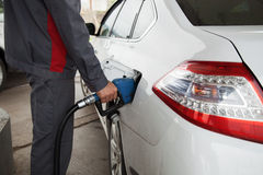 Male hand pumping petrol into car at gas station Stock Images