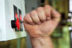 Male hand pushing emergency stop button. Royalty Free Stock Photos