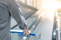 Male hand pushing shopping cart on travelator. Male hand shopper pushing shopping cart trolley on travelator escalator in supermarket or grocery store. Shopping Royalty Free Stock Images