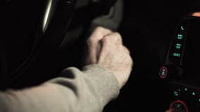 Male hand puts car key into socket and starts engine. Colorful lights on control panel, close up stock footage