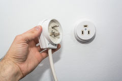 Male hand puts plug in the socket Royalty Free Stock Image