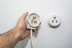 Male hand puts plug in the socket Royalty Free Stock Photos