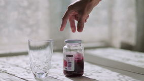 Male hand puts on the table an empty glass, raspberry jam and yogurt stock video footage