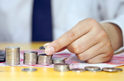 Male hand putting coins into columns Royalty Free Stock Photos