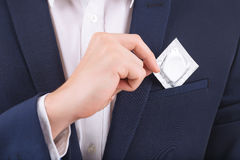 Male hand putting condom into breast pocket Royalty Free Stock Photos