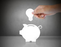 Male hand putting light bulb into a piggy bank Stock Images