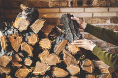 Male hand putting log on pile of stacked firewood Royalty Free Stock Photo