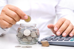 Male hand putting money coins into glass jar bank Royalty Free Stock Photo