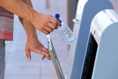 Male hand putting plastic bottle in recycling bin Royalty Free Stock Photo