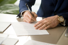 Male hand putting signature on contract, signing document, close. Businessman having signatory right signing contract concept, focus on male hand putting Royalty Free Stock Image