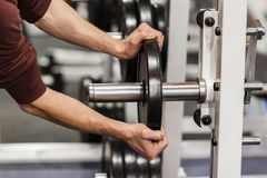 Male hand putting weight plate on barbell Royalty Free Stock Photography