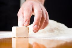 Male hand reaching yeast cube on baking table. Male hand reaching yeast cube on a baking table stock images
