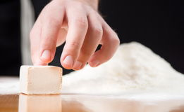 Male hand reaching yeast cube on baking table Royalty Free Stock Photo