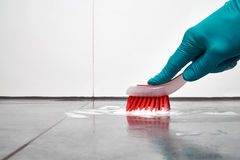 Male hand with red brush cleaning the bathroom tiles on the floor. Royalty Free Stock Images