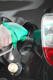 Male hand refilling the black car with fuel on a filling station Stock Photo