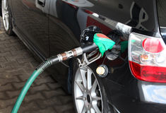 Male Hand Refilling the black Car with Fuel on a Filling Station Stock Images