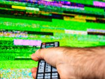 Male hand remote control searching for good signal on tv stock image