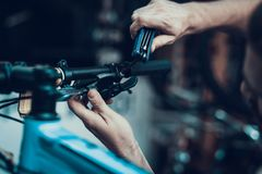 Male Hand Repair Bicycle And Hold Hex Key Wrench. Closeup of Mechanics Muscular Hand Examining and Fixing Modern Cycle Brake System. Bike Maintenance and Sport stock photo