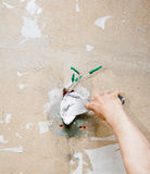 Male hand repairs wall with spackling paste. Stock Photo
