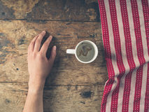 Male hand resting on table with tea towel and cup. A male hand resting on a wooden table with a red and white tea towel and an empty cup Royalty Free Stock Photo