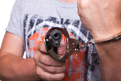 Male hand robber in handcuffs with a gun Royalty Free Stock Photo