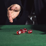 Male hand rolling five dice. On green felt Stock Photo