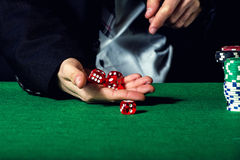 Male hand rolling five dice. On green felt Royalty Free Stock Photos