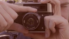 Male hand rotate the camera lens. the photographer sets up the camera before shooting. the operator changes the focus on. The camera. Hand hold a camera lens HD stock video