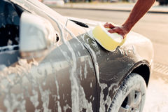 Male hand rubbing the car with foam, carwash. Male hand rubbing the car with foam, automobile in suds. Carwash station Stock Photo