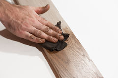 Male hand rubbing oil paint into piece of wood. Stock Photo