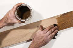 Male hand rubbing oil paint into piece of wood. Royalty Free Stock Photography
