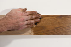 Male hand rubbing oil paint into piece of wood. Royalty Free Stock Image