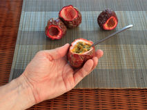 Free Male Hand Scooping Out Passionfruit Against Bamboo Mats Stock Photos - 58130853