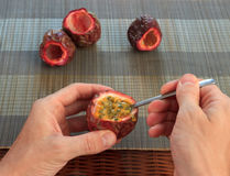 Male hand scooping out passionfruit against bamboo mats Royalty Free Stock Photo