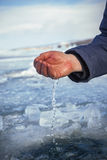 Male hand scoops water from the hole of the lake Stock Photos