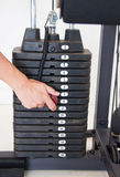 Male Hand Select Weight Of Gym Equipment. Stack Of Metal Weights Bodybuilding Equipment Stock Image