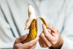 Man in shirt clean banana. Male hand in a shirt holding a ripe banana and clean it royalty free stock photo