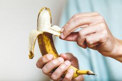 Man in shirt clean banana. Male hand in a shirt holding a ripe banana and clean it stock images