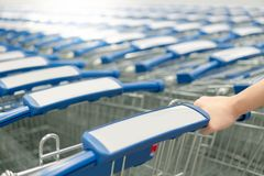 Male hand pulling shopping cart in supermarket. Male hand shopper pulling shopping cart trolley from row in supermarket or grocery store. Shopping lifestyle Royalty Free Stock Photography