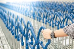 Male hand pulling shopping cart in warehouse. Male hand shopper pulling shopping cart trolley from row in warehouse. Shopping warehousing lifestyle concept Royalty Free Stock Photos