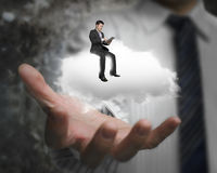 Male hand showing businessman sitting on white cloud Royalty Free Stock Image